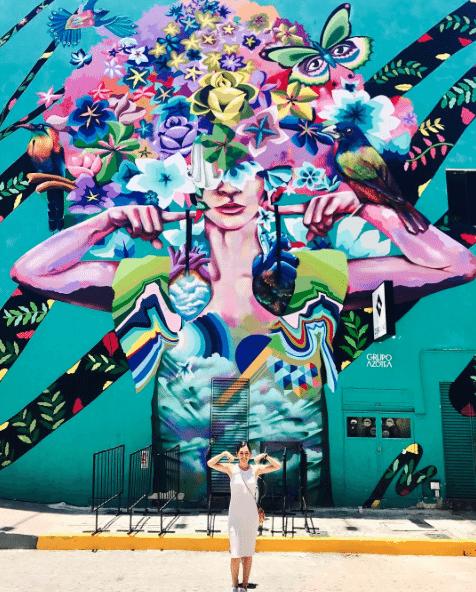 persona mirando uno de los murales de playa del carmen